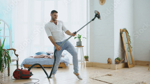Obraz Young man having fun cleaning house with vacuum cleaner dancing like guitarist - fototapety do salonu