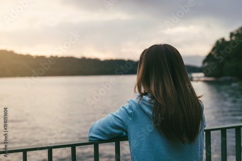 Lonely woman standing absent minded at the river Poster