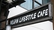 Vegan Lifestyle Cafe Sign Outdoors. Closeup. 4K.