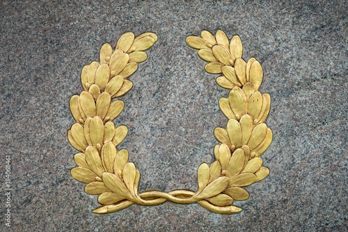 Fotografie, Obraz  Classic laurel wreath symbol with vintage gold leaf detail on textured raised re