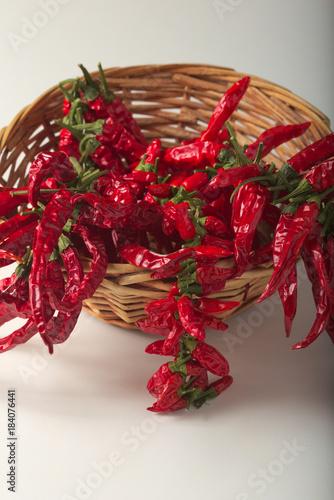 Staande foto Hot chili peppers Peperoncino rosso piccante macinato nel vasetto di vetro, con peperoncini sani essiccati nel cesto.