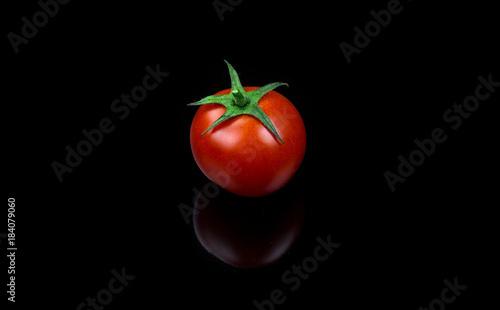 Fresh cherry tomato single on black background