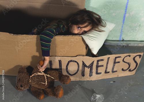 Fotografie, Obraz Depressed homeless kid girl sitting in the cardboard and holding teddy bear