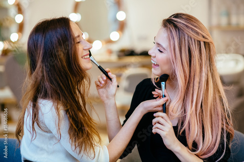 Fotografía  Makeup, friendship and leisure concept - two smiling womenlaughing and playing with brush - applying make up to each other
