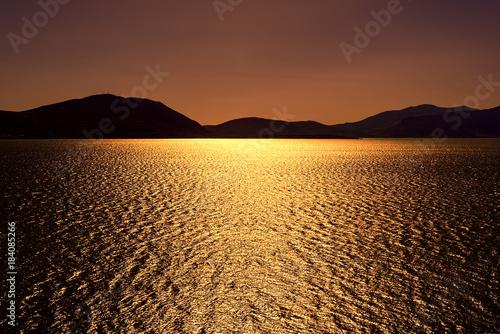 Fototapeta Dark bronze sunset with sun shimmering sun reflections on lake u obraz