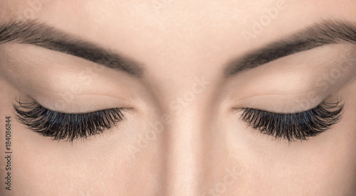 Obraz Eyelash extension procedure. Beautiful Woman with long lashes in a beauty salon. - fototapety do salonu