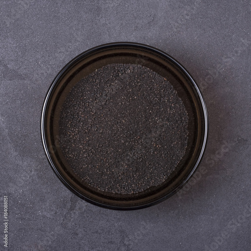 Black cumin powder in a bowl on a grey concrete background