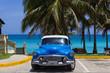Amerikanischer blauer Buick Oldtimer parkt am Strand unter Palmen in Varadero Cuba - Serie Cuba Reportage