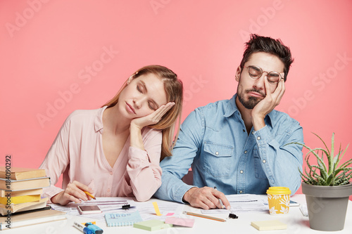 Fotografia Portrait tired crew of office workers sit at table, fall asleep after working long hours on preparing startup project, feel tiredness, isolated over pink background