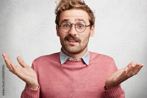 Fotomural  Clueless doubtful male wonk wears round spectacles, shrugs shoulders in bewilderment as doesn`t know answer on question, hesitates, isolated over white concrete background