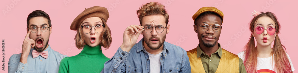 Fototapeta Composition of five different people wear spectacles, look with surprised expression, beig from various nations, express shock and disbelief. Women and men stand in row isolated on pink background