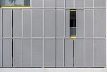 Modern Gray Facade Of Urban Building With Sun Protect Sliding Metal Panels On Windows