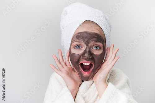 Foto op Aluminium Spa Best result. Portrait of surprised pretty girl is standing with towel on head and white bathrobe and looking at camera with astonishment. She is holding hands near face with clay mask. Isolated