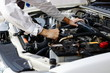Hands of auto mechanic man with wrench repairing engine of motor under car hood. Insurance concept.