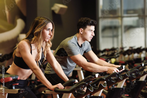 Couple in a spinning class wearing sportswear. Obraz na płótnie