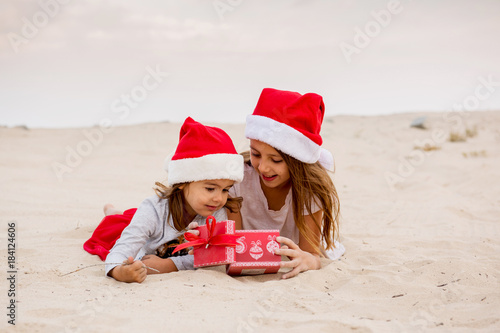 Photo  Two young girls open their festive gift on the beach
