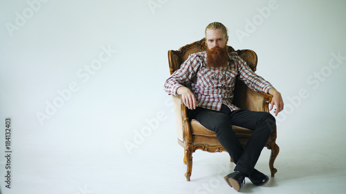 Fényképezés  Bearded man sitting luxury armchair and looking into camera on white background