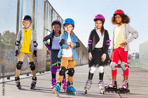 Happy schoolboy rollerblading with mates outdoors