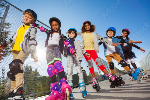 Happy kids rollerblading with hands like wings