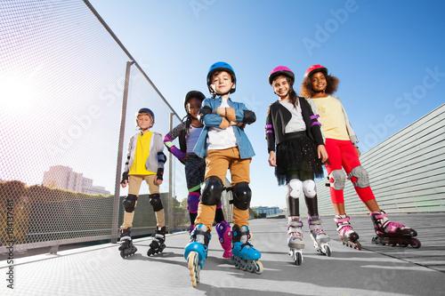 Happy multiethnic kids in rollerblades  outdoors