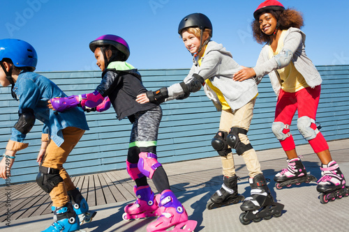 Happy friends having fun while rollerblading