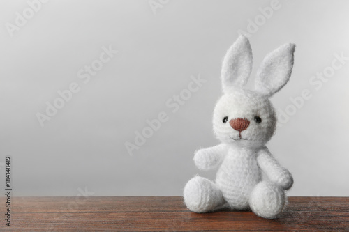 Obraz Cute knitted bunny toy on table against light background - fototapety do salonu