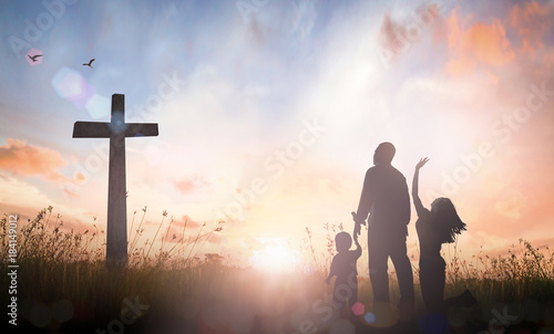 Family worship concept: Silhouette father mother and son looking for the cross on autumn sunrise background Wallpaper Mural