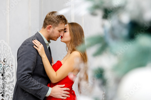 Young couple kiss in evening outfits (jacket and red dress