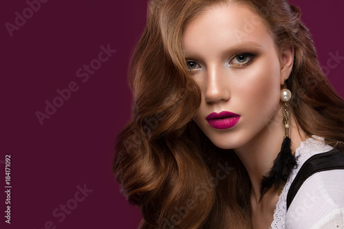 Valokuva  Beautiful redhair model: curls, bright makeup, jewelry and red lips