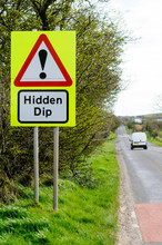 Roadsign On A Rural Road Warning Of A Hidden Dip In The Road