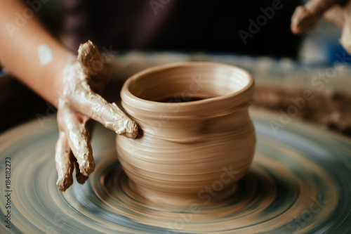 Slika na platnu Hands of young potter, close up hands made cup on pottery wheel