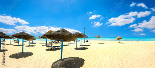 Fotografia  Sunshades on the sandy beach at sunny day