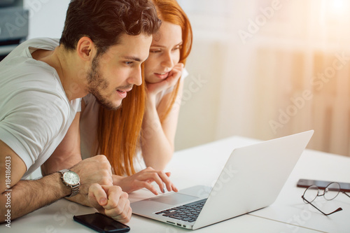 young Couple Using Laptop On Desk At Home and think