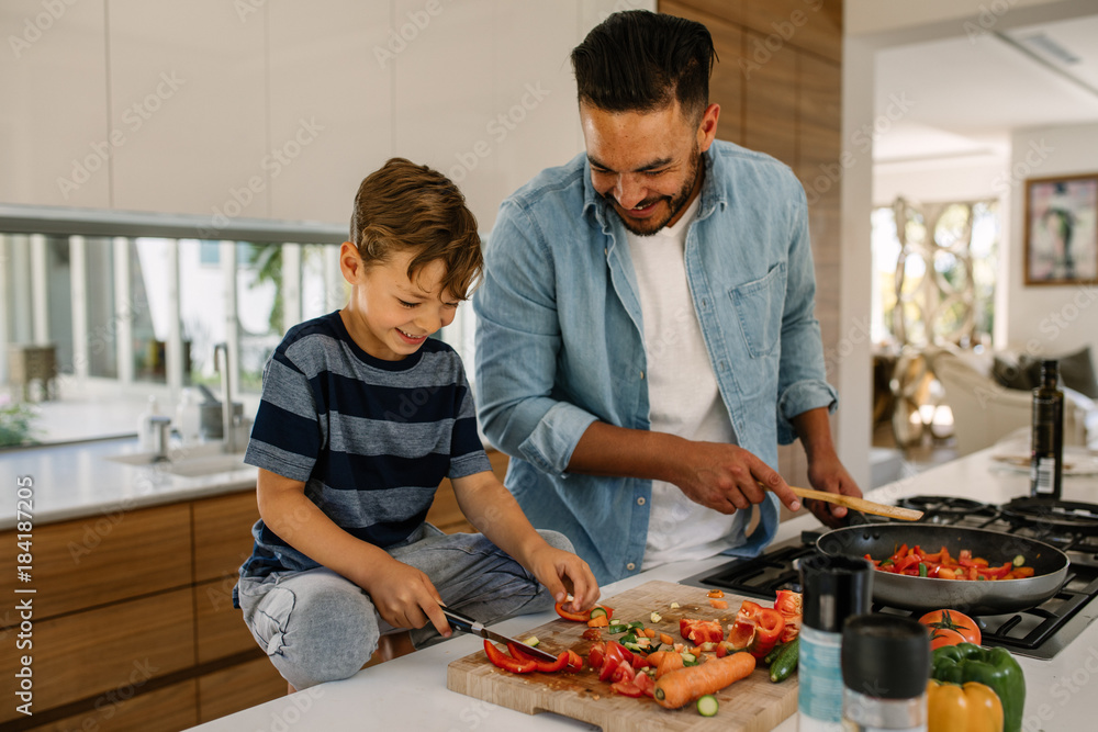 Fototapety, obrazy: Father and son preparing food in kitchen