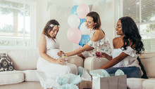 Female Touching Tummy Of Pregnant Woman At Baby Shower