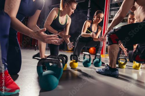Fotografie, Obraz  Group of men and women preparing to kettlebell exercise