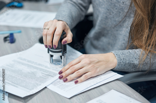 Fotografering girl puts a stamp on documents in the office