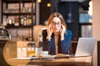 Young businesswoman having headache while working with laptop at the modern cafe interior