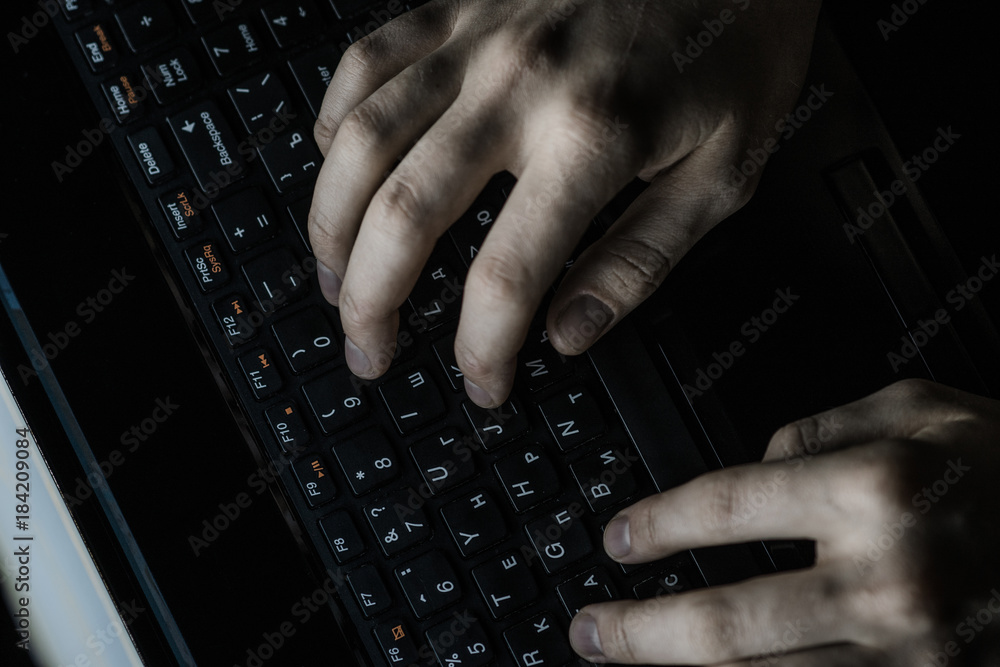 Fototapeta Male computer hacker wearing a hooded top leaning over a laptop in the dark. The screen light illuminates the man with a beard performing illegal activities. Black copy space on the left
