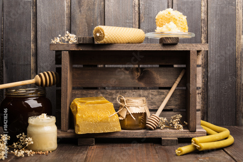 Still life of apicultural products with wax, candles and honey Canvas Print