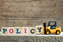 Yellow Toy Forklift Hold Letter Block Y To Complete Word Policy On Wood Background