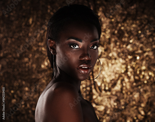 portrait of sensual young african woman against golden background - fototapety na wymiar