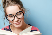 Young Woman Reads A Book On A Blue Background