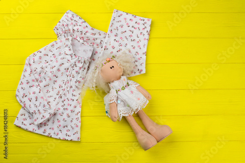 Girls clothes and stuffed doll on yellow wooden background. Top with floral  print and ruffles 2aa061e92