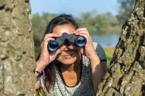 Woman looking through binoculars near trees