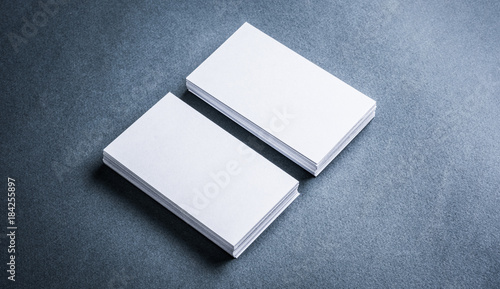 Fotografía  Two stacks of blank paper business cards on textured background.