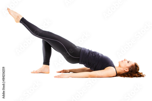 Obraz na plátně Young fit woman doing pilates excercises isolated on white background