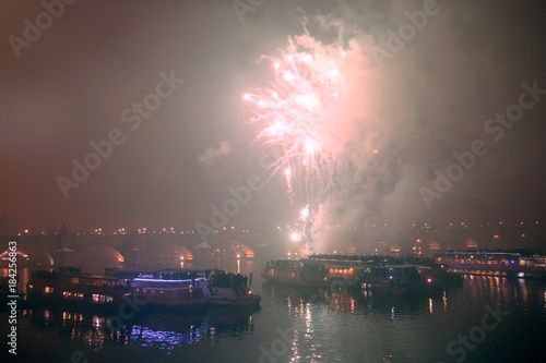 Photo Stands Night blue Fireworks on New Year's Eve over ships on the Vltava River in Prague