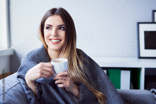 Obraz Cheerful young woman drinking coffee sitting under blanket on sofa at home - fototapety do salonu