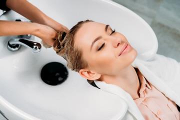 izrezana slika frizera koji kupacu pere kosu šamponom